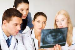Группа в составе доктора смотря рентгеновский снимок Стоковые Фото