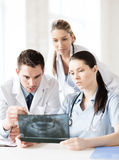 Группа в составе доктора смотря рентгеновский снимок Стоковые Изображения