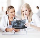 Группа в составе доктора смотря рентгеновский снимок Стоковое Фото