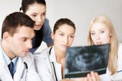 Группа в составе доктора смотря рентгеновский снимок Стоковое Изображение