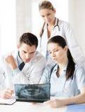 Группа в составе доктора смотря рентгеновский снимок Стоковая Фотография