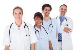 Группа в составе доктора стоя совместно над белизной Стоковая Фотография