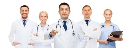 Группа в составе доктора с доской сзажимом для бумаги указывая на вас Стоковое Фото