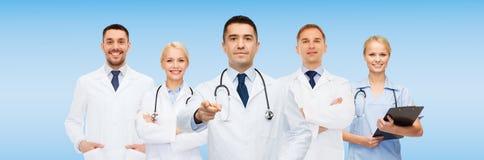 Группа в составе доктора с доской сзажимом для бумаги указывая на вас Стоковое фото RF