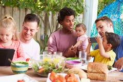 Группа в составе отцы при дети наслаждаясь внешней едой дома стоковые изображения rf