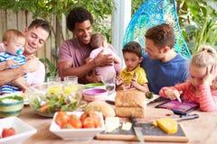 Группа в составе отцы при дети наслаждаясь внешней едой дома стоковые фотографии rf