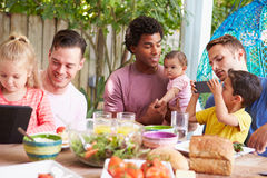 Группа в составе отцы при дети наслаждаясь внешней едой дома стоковые фото