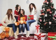 Группа в составе очень молодые женщины говорит о подарках внутри Стоковое Фото