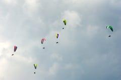 Группа в составе парапланы летает в день лета солнечный Карпаты, Украина Парапланы на фоне облаков Стоковые Фото