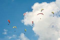Группа в составе парапланы летает в день лета солнечный Карпаты, Украина Парапланы на фоне облаков Стоковая Фотография