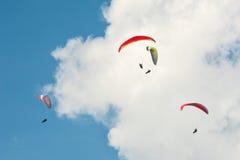 Группа в составе парапланы летает в день лета солнечный Карпаты, Украина Парапланы на фоне облаков Стоковое фото RF