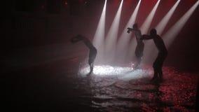 Группа в составе парни танцует активный танец в воде с брызгает в луче фары видеоматериал