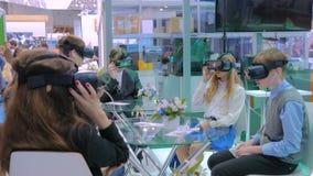 Группа в составе подростки используя шлемофон виртуальной реальности на выставке технологии акции видеоматериалы