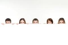 Группа в составе подростки пряча за белым знаменем стоковые изображения