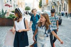Группа в составе подростки с хозяйственными сумками на улице города стоковая фотография