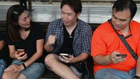 Группа в составе подросток сидит на стенде и использует их умные телефоны