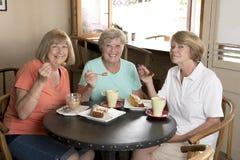 Группа в составе 3 подруги женщин симпатичных старшия среднего возраста зрелых встречая для кофе и чая с тортами на кофейне деля  Стоковые Изображения RF