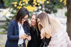 Группа в составе 4 подруги смотря телефон на selfie они w Стоковая Фотография