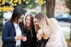Группа в составе 4 подруги смотря телефон на selfie они w Стоковые Фотографии RF