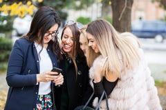 Группа в составе 4 подруги смотря телефон на selfie они w Стоковые Фото