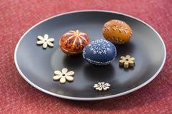 Группа в составе 3 покрашенных воском пасхального яйца распространила на черной плите, орнаментах цветка, традиционном украшении Стоковая Фотография RF
