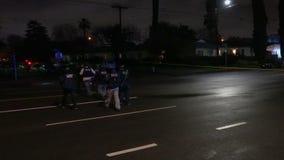 Группа в составе полиция пересекая улицу вечером во время тупика видеоматериал