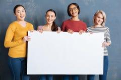 Группа в составе положительные радостные женщины держа плакат стоковое изображение rf