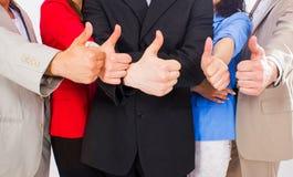 Группа в составе портрета бизнесмены стоя совместно в офисе. Они поднимали большие пальцы руки вверх. Стоковая Фотография