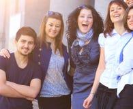Группа в составе положение студентов колледжа усмехаясь дружелюбное рядом друг с другом, на солнечный день Стоковое Изображение RF