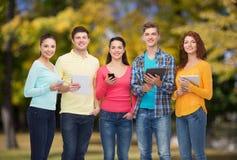 Группа в составе подростки с smartphones и ПК таблетки Стоковое Изображение