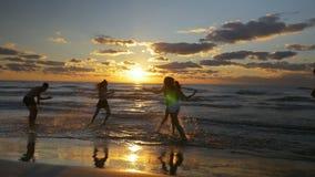 Группа в составе подростковые друзья бежать и играя в воде на пляже видеоматериал