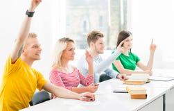 Группа в составе подростковые студенты поднимая руки Стоковая Фотография RF
