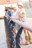 Группа в составе подруги используя smartphone в городе Стоковое Изображение