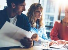 Группа в составе предприниматели ищет решение дела во время процесса работы на солнечном офисе Молодое белокурое использование же Стоковые Изображения