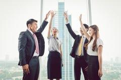 Группа в составе предприниматели поднимая их руки стоковое изображение rf