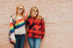Группа в составе 2 прелестных девушки ребенк с школой укладывает рюкзак нося стекла Стоковые Изображения