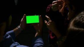 Группа в составе предназначенный для подростков смеяться над и иметь потехой пока наблюдающ зеленый smartphone экрана видеоматериал
