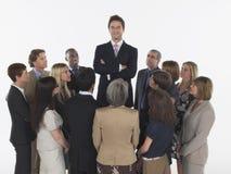 Группа в составе предприниматели вытаращить на высокорослом человеке стоковые изображения