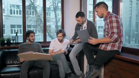 Группа в составе предприниматели работая и принимая примечания совместно в маленький офис Встреча фрилансера, человек с питьем ко Стоковые Изображения