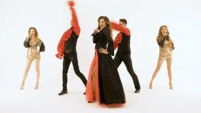 Группа в составе профессиональные актеры танцуя на белой предпосылке Певица девушки в черном платье 2 молодого человека в черноте акции видеоматериалы