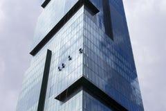 Группа в составе работники очищает окна небоскреба высокого подъема современного Стоковое фото RF
