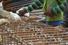 Группа в составе рабочий-строители изготовляя бар подкрепления крышки кучи стальной Стоковое Фото