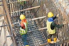 Группа в составе рабочий-строители изготовляя бар подкрепления крышки кучи стальной Стоковая Фотография RF