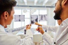 Группа в составе радиологи анализируя изображение рентгеновского снимка Стоковые Изображения RF