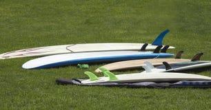 Группа в составе различные surfboards кладя на траву на прибрежном Стоковая Фотография RF