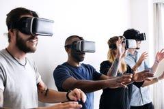 Группа в составе разнообразные друзья испытывая виртуальную реальность с шлемофоном VR стоковое изображение