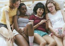 Группа в составе разнообразные женщины лежа на кровати используя мобильные телефоны совместно стоковое изображение