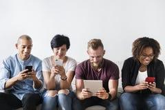 Группа в составе разнообразные люди используя приборы цифров стоковое изображение
