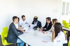 Группа в составе разнообразные руководители бизнеса созывая собрание вокруг таблицы обсуждая диаграммы показывая статистический а стоковое фото