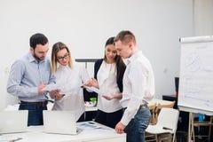 Группа в составе 4 разнообразных люди и женщины в вскользь одежде говоря в офисе Стоковые Фотографии RF